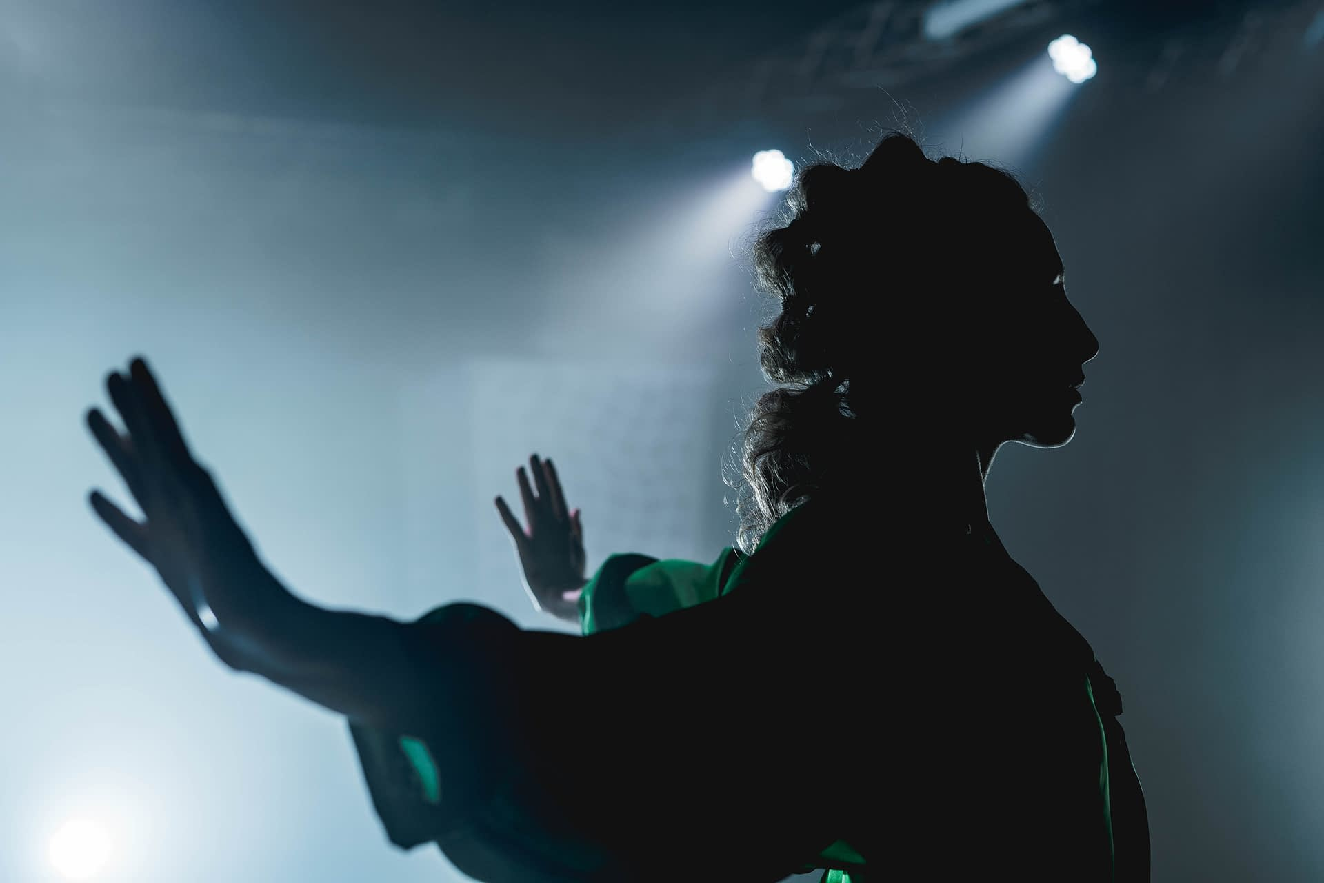 Profile of a woman dancing in shadow with her arms spread wide