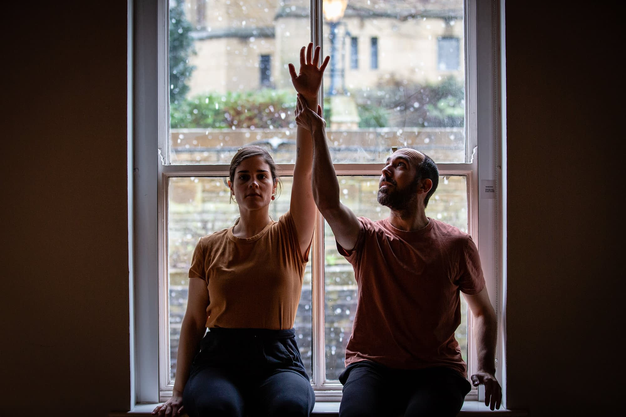 A man and a woman sit side by side in front of a window, each raising a hand above their heads to meet in the middle.